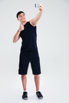 Portrait of a fitness man making selfie photo on smartphone isolated