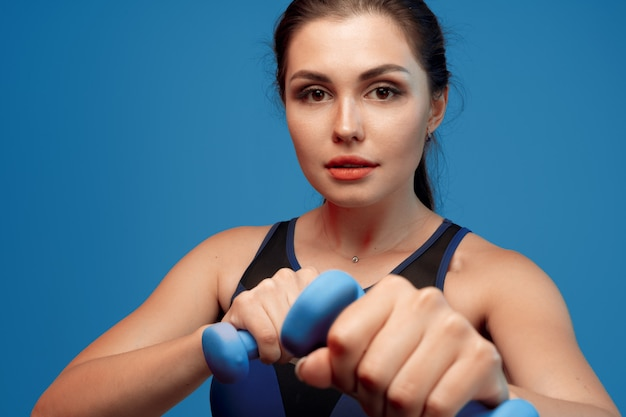 Portrait of a fitness model working out with dumbbells on grey background