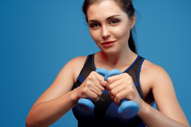 Portrait of a fitness model working out with dumbbells on grey