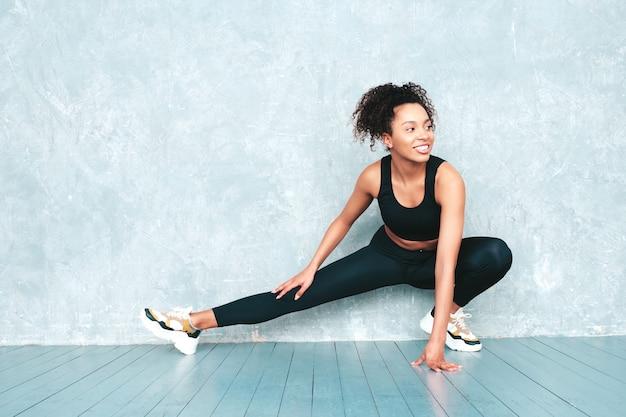 Ritratto di fitness donna sorridente in abbigliamento sportivo con acconciatura afro ricci