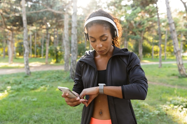 Portrait of fitness woman 20s wearing black tracksuit and headphones, looking at wrist watch while walking through green park