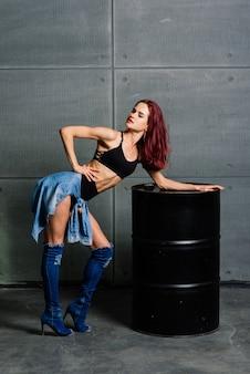Portrait of fitness woman on cement concrete background, near a black barrel.