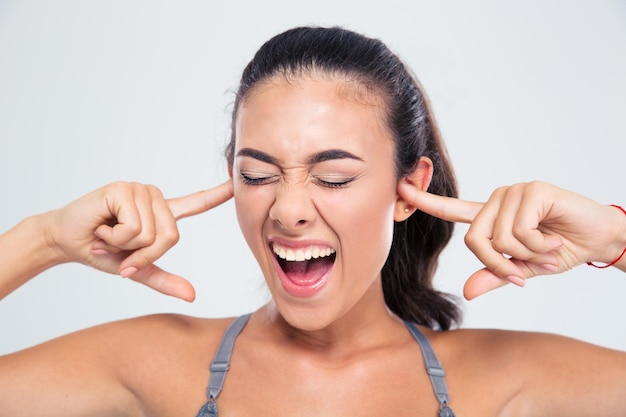 Portrait of a fitness woman covering her ears with fingers and shouting isolated on a white wall