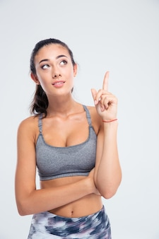 Portrait of a fitness woman pointing finger up isolated on a white wall