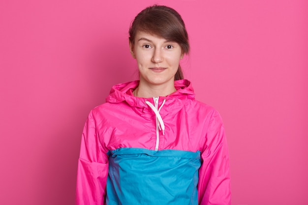 Portrait of fitness woman posing after working out in gym, wearing blue and pink sportwear, looking directly at camera, having dark hair