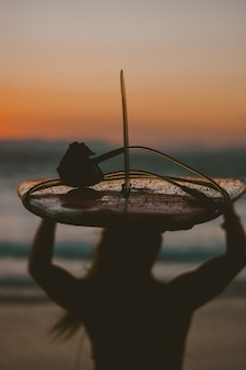 Портрет фитнес женщина позирует с доски для серфинга на пляже на закате с силуэтом