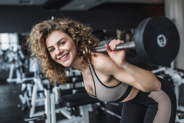 Portrait of a fitness young girl doing squats with barbell at the gym