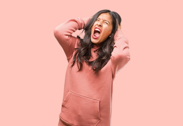 Portrait of fitness young indian woman crazy and desperate, screaming out of control