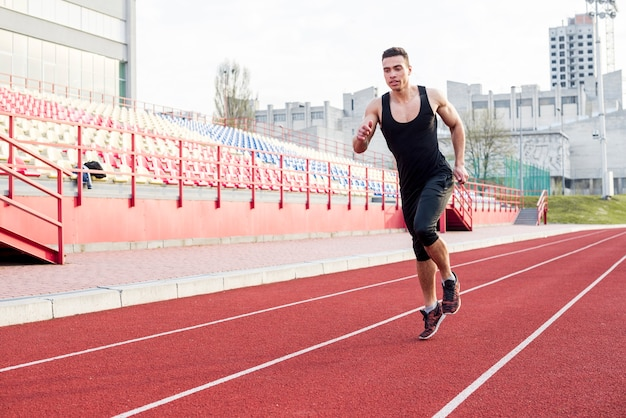 Portrait of fitness young male athlete running on race track in the stadium