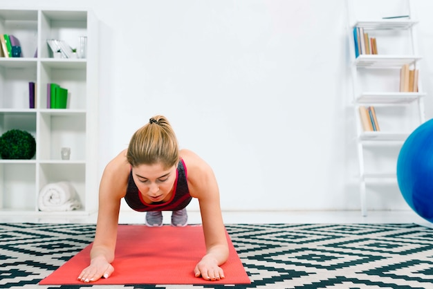 Portrait of fitness young woman doing core exercise on fitness mat in the gym