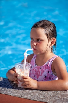 Portrait of a fiveyearold girl in a pink swimsuit enjoying a milkshake at the edge of the hotel pool...