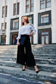Portrait of a flawless young woman in white blouse, wide black pants and classic high heels posing on the stairs with black laptop in her hand with a huge white building