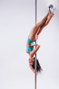 Portrait of a flexible female dancer balancing on pole. isolated on white background