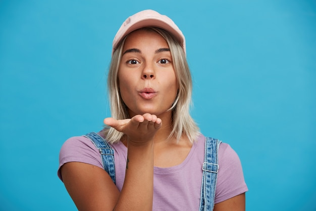 Portrait of flirty attractive blonde young woman wears pink cap and violet t shirt looks playful and sending air kiss isolated over blue wall