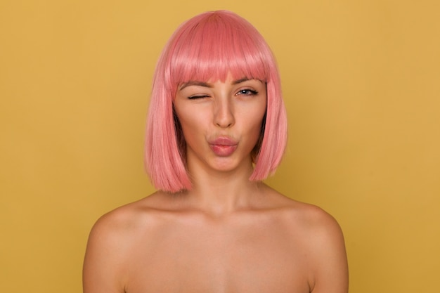 Portrait of flirty pretty young woman with pink bob haircut pouting her lips in air kiss and giving wink while looking positively at camera, posing over mustard wall