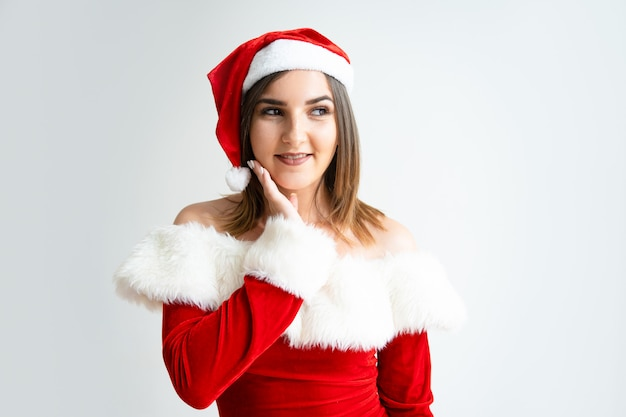 Portrait of flirty woman in santa claus outfit touching face
