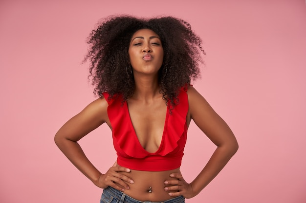 Portrait of flirty young dark skinned female with curly hair holding her waist with amrs and folding lips in kiss, posing on pink in red top and jeans