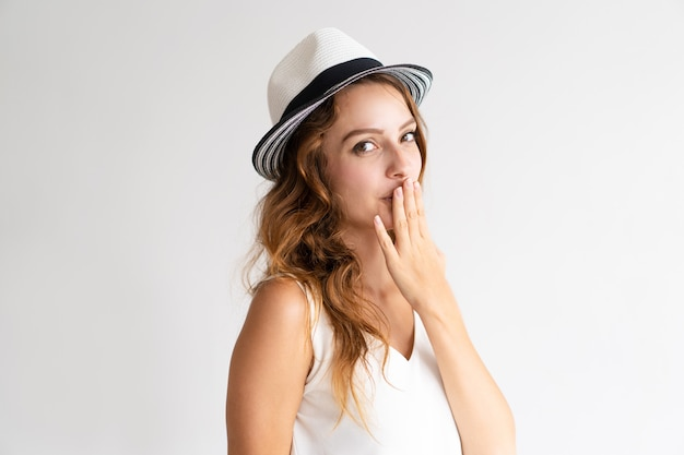 Portrait of flirty young woman in hat covering mouth.