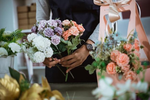 肖像画の花屋は、顧客のためにテーブルのワークスペースでギフトの花を準備します