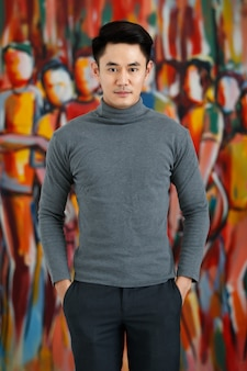 Portrait fo asian man handsome smiling looking away wearing gray long sleeve t-shirt standing on a artistic picture background.