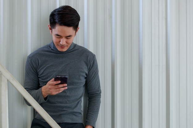 Portrait fo young asian man handsome smiling holding hand smartphone wearing gray long sleeve t-shirt standing and on a stainless steel background.