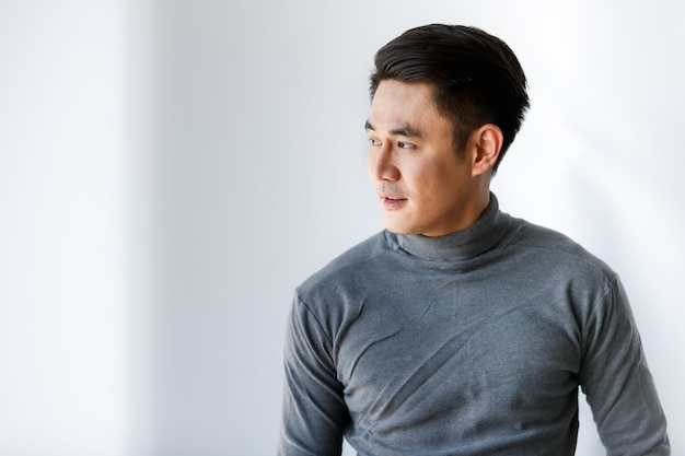 Portrait fo young asian man handsome smiling looking away wearing gray long sleeve t-shirt standing on a white background.