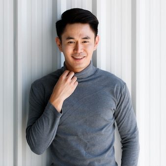 Portrait fo young asian man handsome smiling wearing gray long sleeve t-shirt standing on a stainless steel background.