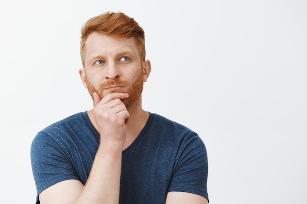 Portrait of focused creative and smart good-looking male strategist with red hair, standing in thoughtful pose, rubbing beard and gazing aside while thinking, making up plan in mind