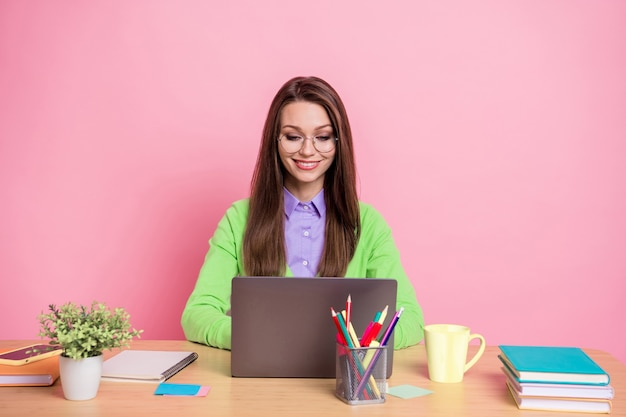 Portrait of focused girl sit table work laptop wear green shirt isolated over pastel color background