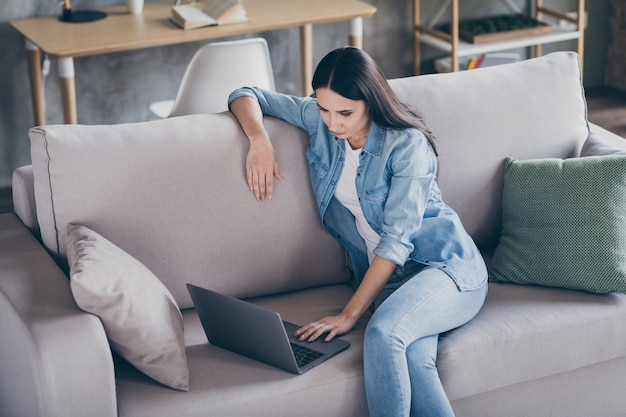 Portrait of focused manager girl work home office use laptop read collar ceo startup report watch coaching online training study sit divan in house indoors