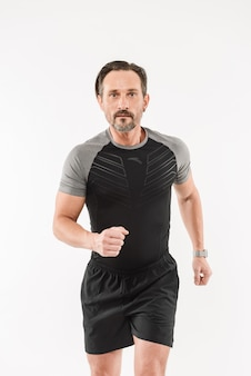 Portrait of focused motivated adult man 30s wearing sportswear having lot of stamina running marathon or doing workout