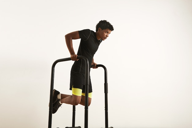 A portrait of a focused muscular african american young man in black workout clothes doing dips on parallel bars on white