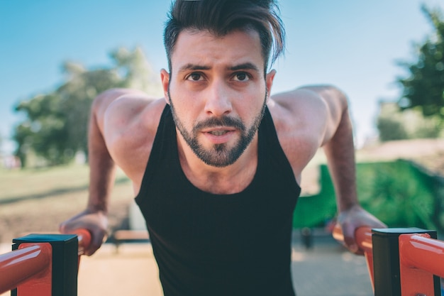 A portrait of a focused muscular bearded man in black workout clothes doing dips on parallel bars  m