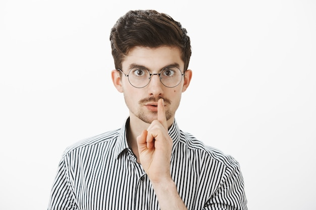 Portrait of focused serious nerdy guy in round glasses, saying shh while making shush gesture with index finger over mouth, feeling nervous friend will tell secret