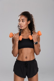 Portrait of a focused young african sportswoman doing exercises with dumbbells isolated over grey background