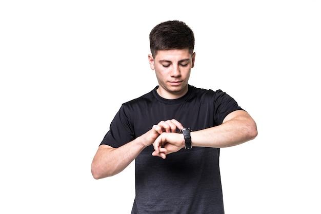 Ritratto di un giovane sportivo concentrato che adegua il suo orologio da polso isolato su bianco