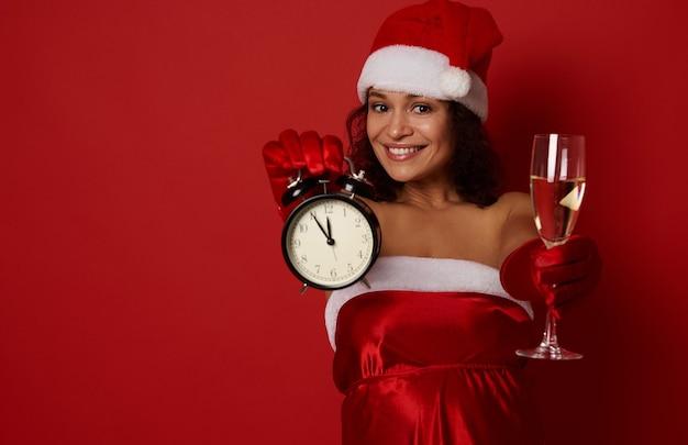 Портрет для рекламы привлекательной женщины в шляпе и платье санта-клауса, держащей бокал с игристым вином и показывающей время на будильнике в руках, за пять минут до новогоднего и рождественского праздника.