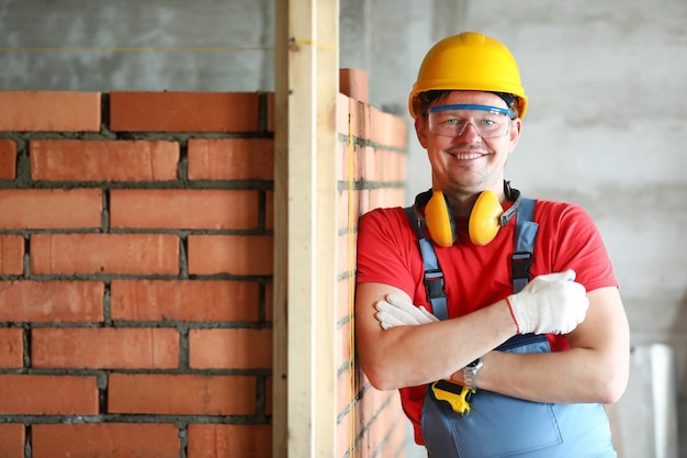 Portrait of foreman at construction site. laborer wearing protective helmet, gloves and headphones. handyman building or fixing, mortar or mason at work