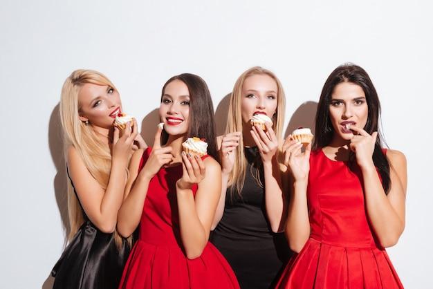 Portrait of four happy attractive young women tasting cupcakes over white background
