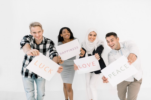 Portrait of four happy funny multiracial friends standing over white wall