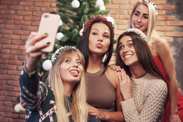 Portrait of four smiling girl with corolla on the head make selfie photo. new year's feeling. merry christmas