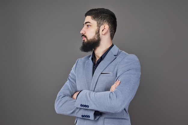 Portrait of freelancer man with beard in jacket standing against gray backdrop