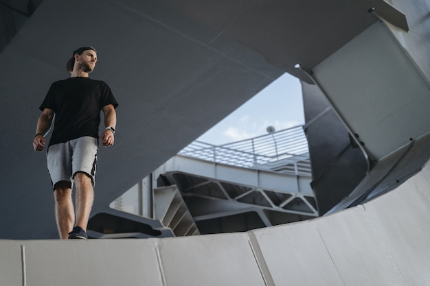 Portrait of freerunning athlete standing on the edge metal construction. looking at place for your advertise