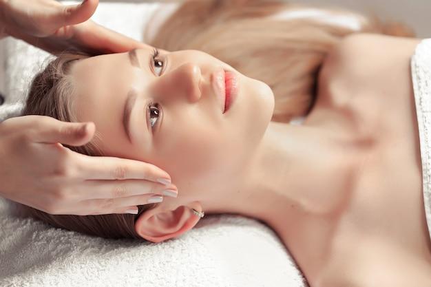 Portrait of fresh and beautiful brunette woman taking face massage