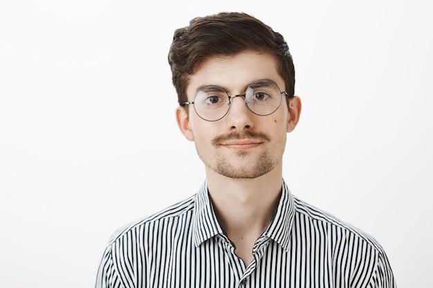 Ritratto di ragazzo barbuto caucasico fiducioso amichevole con i baffi, con gli occhiali, sorridente educatamente e guardando rilassato e calmo sul muro grigio, ascoltando il reclamo del cliente sul muro grigio