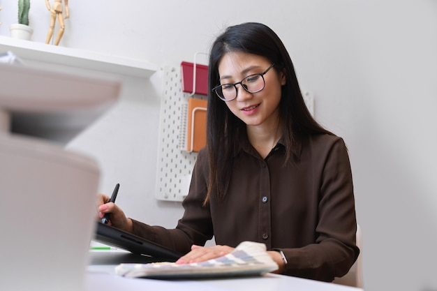 Portrait of friendly female designer smiling and working with designer supplies in office room