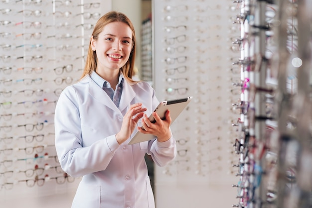 Portrait of friendly female optometrist using tablet
