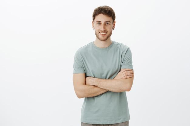 Ritratto di amichevole gioiosa collega maschio in abito casual in piedi con le braccia incrociate e sorridente con amichevole espressione felice mentre aspetta che la moglie si vesta per camminare