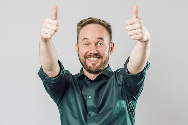 Portrait of friendly man raising thumbs up