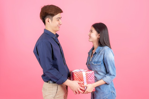Portrait friendly teenage man and woman , they are place red gift box and smiling with funny, teenage asian couple concept